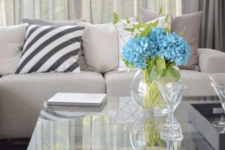 luz natural: Luz de flores y vino azules gafas en mesa de centro con rayas almohada blanco y negro y cojines de tonos grises en el sofá de color beige