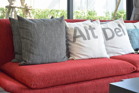red sofa: modern living room design with pillows on the red sofa and decorative lamp