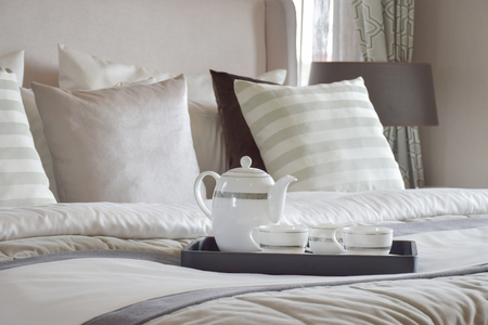 breakfast in bed: Decorative tray of tea set on the bed in modern bedroom interior