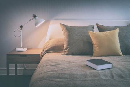 lamp: vintage style photo of cozy bedroom interior with book and reading lamp on bedside table