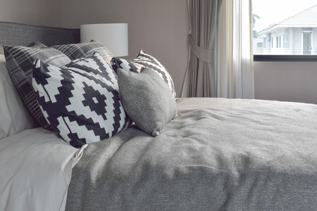 wooden bed: Graphic style and grey shade pillows on classic color bedding set up Stock Photo