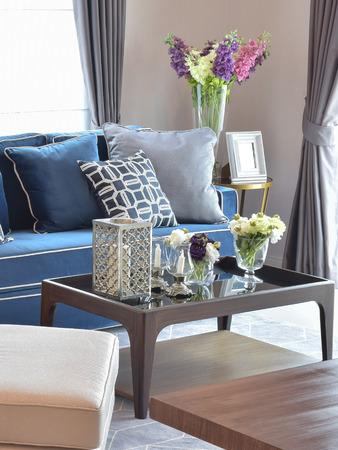 Romantische kaars set met beige en blauwe moderne klassieke bank in warme woonkamer Stockfoto
