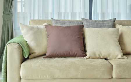 brown leather sofa: Brown pillows on light brown leather sofa