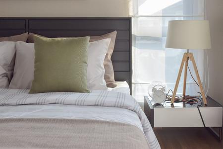 chambre à coucher: intérieur d'une chambre moderne avec coussin vert et lampe en bois décoratif sur la table de chevet Banque d'images