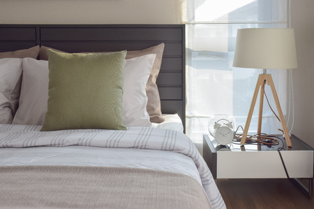 bedroom: modern bedroom interior with green pillow and decorative wooden lamp on bedside table