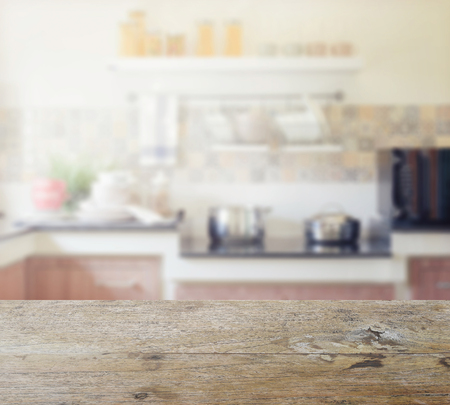 contemporary kitchen: wooden table top with blur of modern kitchen interior for background Stock Photo