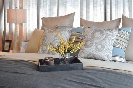 chambre à coucher: chambre de luxe design d'intérieur avec des oreillers rayés et thé ensemble décoratif sur le lit Banque d'images