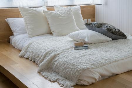 cama: elegante diseño interior del dormitorio con almohadas blancas y negras en la cama.