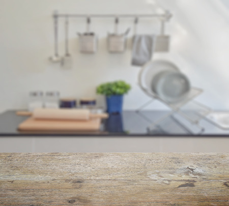 countertop: wooden table top with blur of modern ceramic kitchenware and utensils on the countertop