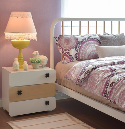 bedside: Cozy bedroom interior with pillows and reading lamp on bedside table Stock Photo