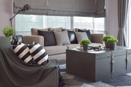 living room design: Striped and black leather pillows on the sofa in modern industrial style living room