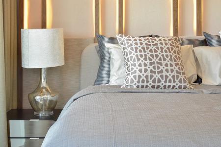 stijlvolle slaapkamer inter ontwerp met bruine kussens op bed en decoratieve schemerlamp.