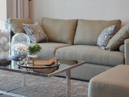 living style: comfortable velvet sofa with grey striped pillows in modern living room Stock Photo