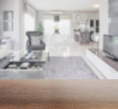 pantry: wooden table top with blur image of modern living room interior with dining table and pantry at home