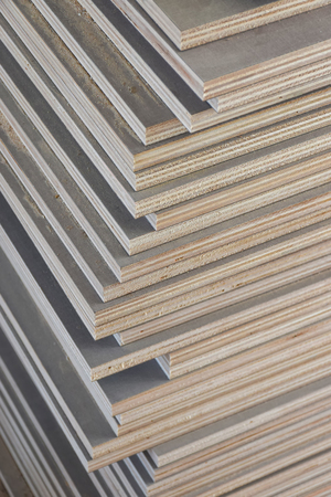 Stack of industrial plywood in construction site for background