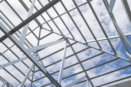 blue steel: Structure of steel roof frame with blue sky and clouds at construction site Stock Photo