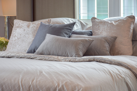bedside lamp: Classic bedroom interior with pillows and reading lamp on bedside table