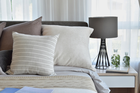 stijlvolle slaapkamer interieur met bruin patroon kussens op bed en decoratieve schemerlamp.