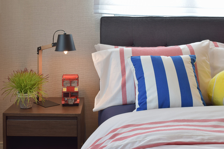 reading lamp: modern bedroom interior with colorful striped pillows and wooden reading lamp on bedside table Stock Photo