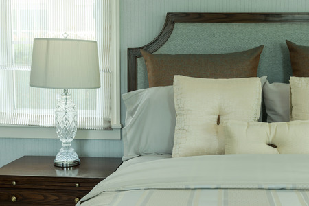 bedside: cozy bedroom interior with white pillows and reading lamp on bedside table