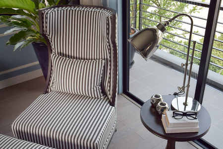 easy chair: black striped easy chair in the corner with decorative brass lamp and books on wooden round table