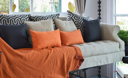 carpet clean: modern living room design with brown and orange tweed sofa and black pillows Stock Photo