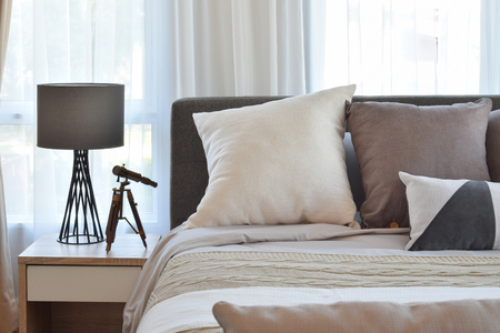 bedroom design: stylish bedroom interior design with brown patterned pillows on bed and decorative table lamp. Stock Photo