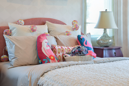 bedside: colorful pillows and bedside table lamp in modern kid bedroom interior