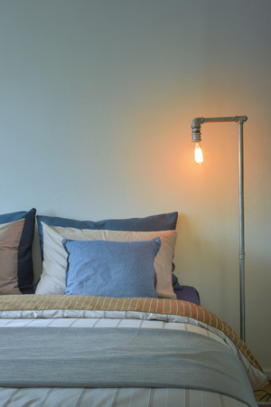reading lamp: Industrial style reading lamp and blue pillows on modern style bedding