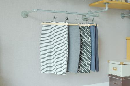 walk in closet: skirts hanging on industrial style clothes rail in walk in closet Stock Photo