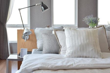 entre diseño elegante dormitorio con almohadas blancas rayas en la cama y la lámpara de tabla decorativa. Foto de archivo