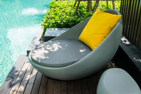 Relaxing chairs with pillows beside swimming pool Stock Photo