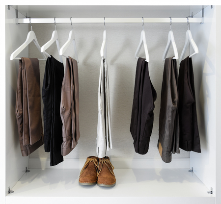 black pants: brown leather shoes and row of black pants hangs in wardrobe