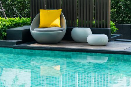 Ontspannen stoelen met kussens naast zwembad Stockfoto