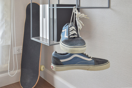 shelve: pair of casual blue sneaker shoes hanging on book shelve at home