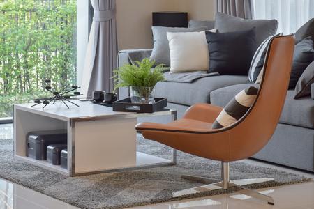植物の花瓶、モダンな革張りの椅子の上に黒いパターン枕付きのリビング ルーム 写真素材