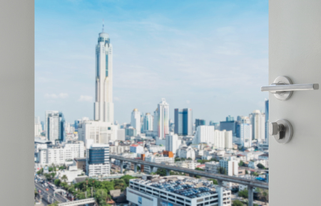 buidings: opened white door to bangkok city skyline with modern buidings as background