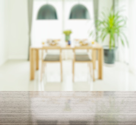 granite table top and blur of wooden dining table and chairs with elegant table setting