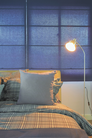 comfy: Floor lamp next to comfy bed in night time