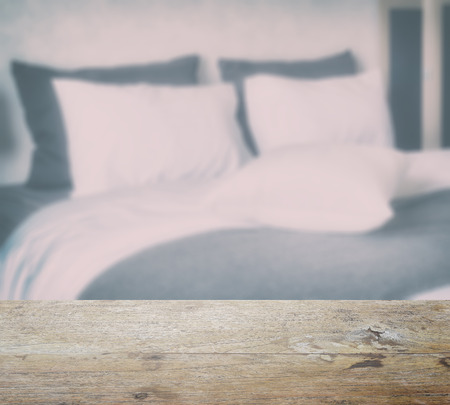 king size: wooden table top and blur of clean bedding with king size bed in modern bedroom interior Stock Photo