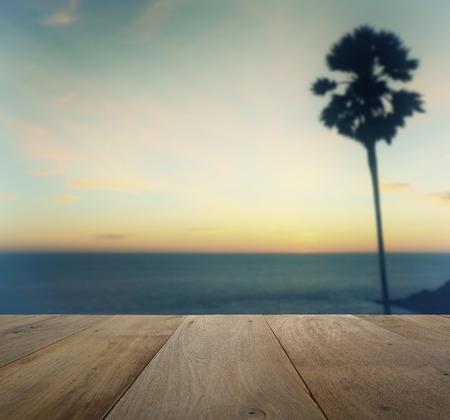 bounty: mesa de madera en la puesta de sol vista borrosa con el árbol de la silueta de palma en la playa tropical Foto de archivo