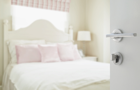 bedspread: opened white door to luxury bedroom with pillows and desk lamp as blur background