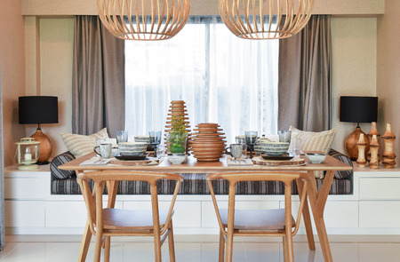dining set: dining wooden table and comfortable chairs in modern home with elegant table setting