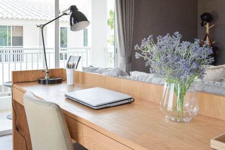working area: wooden table with computer notebook,pencil,lamp and artificial flowers in modern working area at home