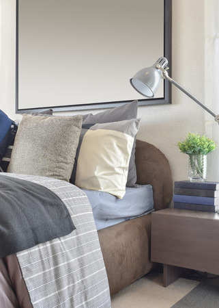 bedside lamp: modern bedroom with gray pillow and lamp on wooden bedside table at home