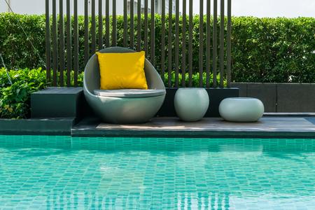 Relajante sillas con almohadas al lado de la piscina Foto de archivo