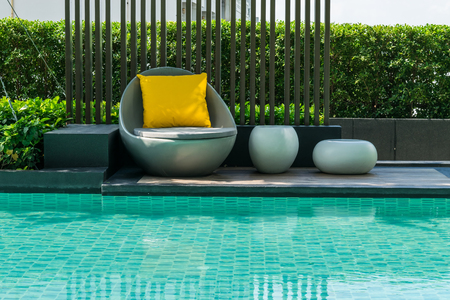 lawn chair: Relaxing chairs with pillows beside swimming pool Stock Photo