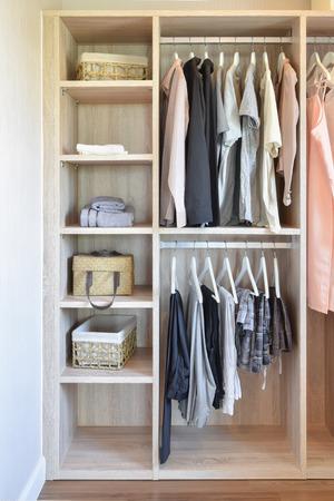 modern closet with row of cloths hanging in wooden wardrobe Standard-Bild