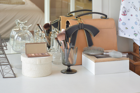 Make up items and leather bag on dressing table Stock Photo