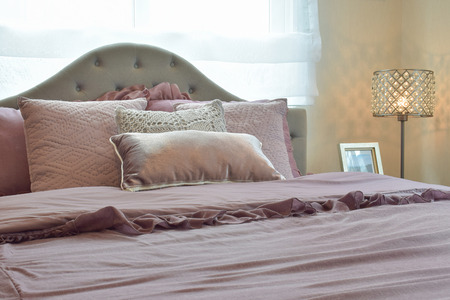 bedside lamp: Cozy  and classic  bedroom interior with pillows and reading lamp on bedside table